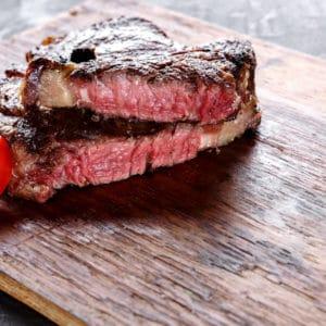 Rare rib eye steak on wooden board, closeup